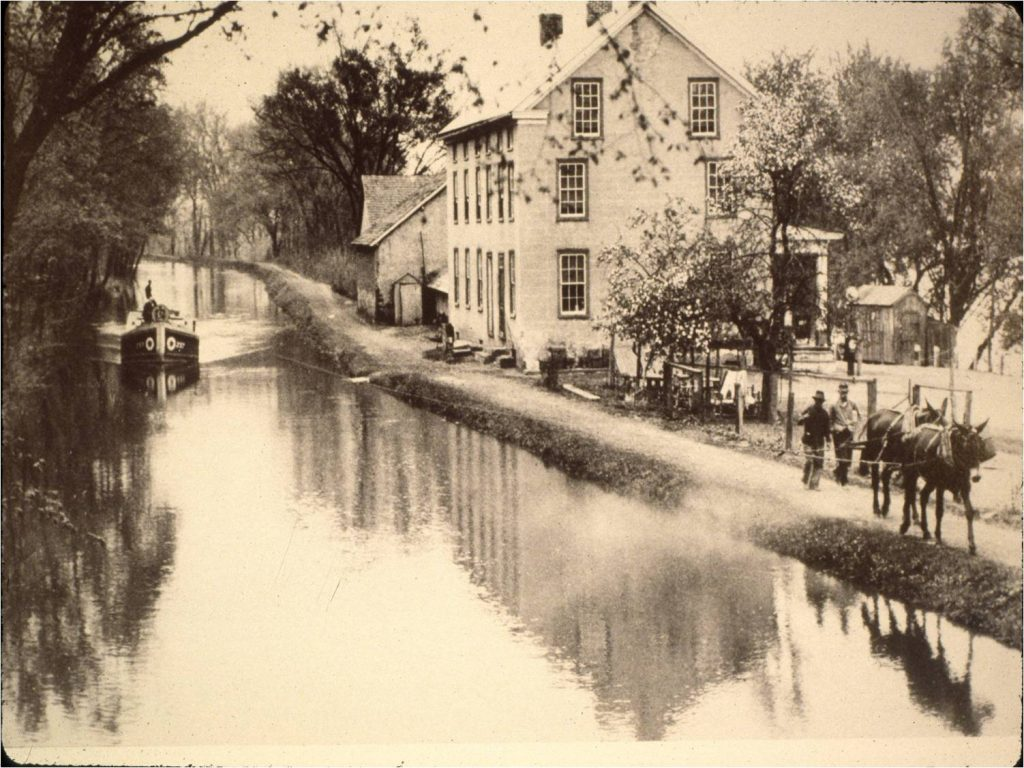 building, house, canal, boat, mules, people, animals, water, reflections, windows, trees, path